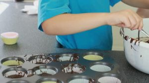 stock-footage-young-boy-baking-cup-cakes-with-his-grandmother-in-the-kitchen